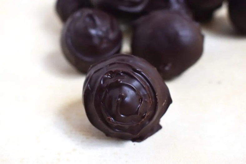 Close up of a chocolate covered Tim Tam Cheesecake Truffles. These are sweet and creamy Tim Tam cheesecake with the distinct flavour of chocolate Tim Tams. If you love Tim Tams and cheesecake you will love these truffles. #timtams #timtamcheesecake