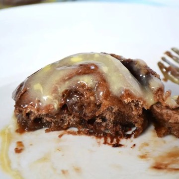 Chocolate Cinnamon Rolls. Soft and fluffy rolls with a touch of cocoa powder added for a slight chocolate flavour with a cinnamon, brown sugar and chocolate chip filling. Covered in an optional cream cheese drizzle! These are soft and fluffy but ooey gooey in the middle. #cinnamonrolls #chocolatecinnamonbuns