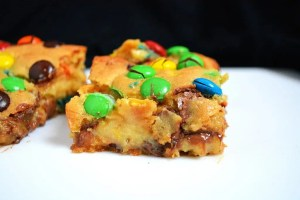 M&M Caramel Cookie Bars are a soft, chewy and ooey gooey chocolate chip cookie baked in a slice pan with a thick layer of sweet and buttery caramel running through the middle. With the addition of M&Ms to take these gooey cookie bars over-the-top and add a pop of colour. #caramelcookiebars #chocolatechipcookiebars