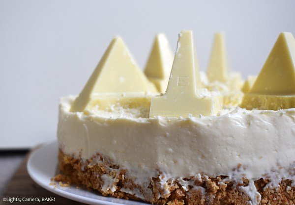 Side view of half of a White Chocolate Toblerone Cheesecake with a white background.