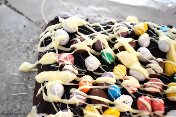 White chocolate drizzled easter mini eggs on a brownie.