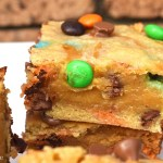 Close up of a caramel filled M&M cookie bars with a brick background on a white plate.