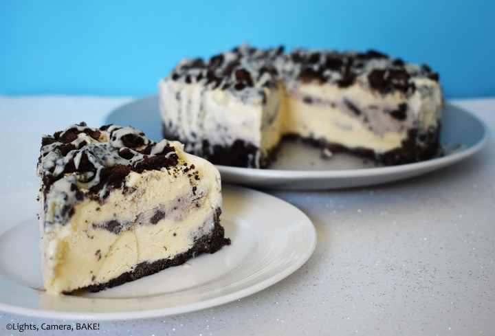 Slice of vanilla and Oreo ice cream cake on a blue background.