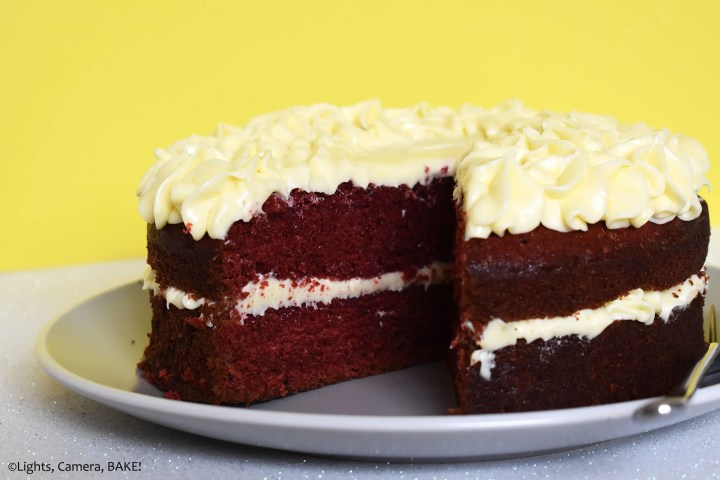 Layered red velvet cake iwth cream cheese icing on a plate.