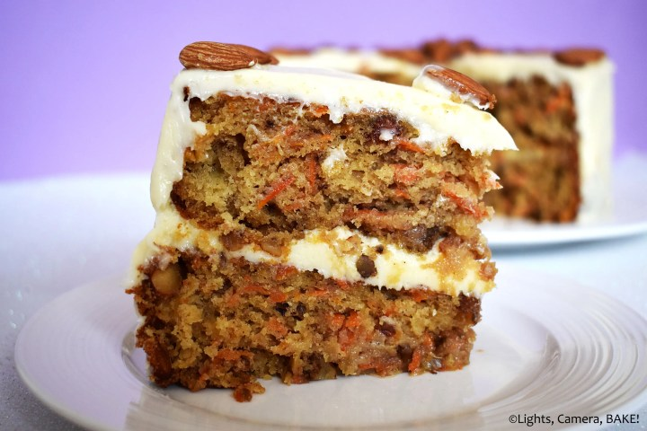 Slice of carrot cake with cream cheese icing on a purple background.
