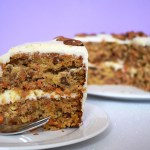 Slice of carrot cake on a purple background.