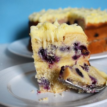 Slice of lemon blueberry cake on a blue background.