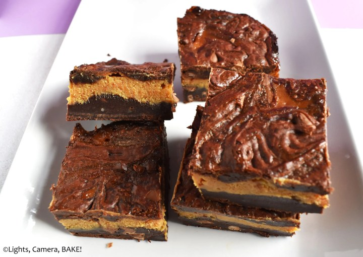 Pieces of caramel stuffed brownies on a plate.