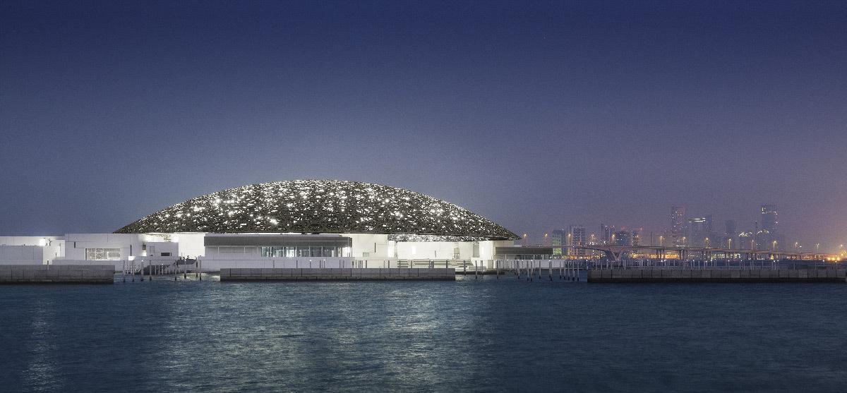 Mise en lumière extérieure du dôme du musée du Louvre Abu Dhabi avec la ville à l'horizon la nuit - Architectes : Jean Nouvel et Hala Warde