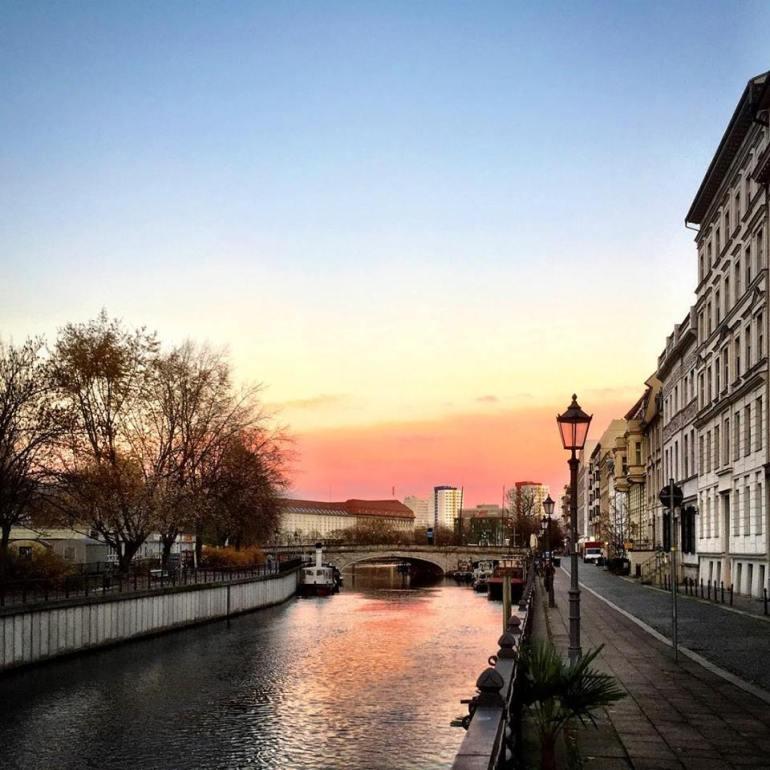 #paracegover Descrição para deficientes visuais: a imagem mostra um canal do rio Spree com uma ponte. Nas laterais, edifícios antigo e uma luminária charmosa. O céu está parte azul e parte rosa pêssego.