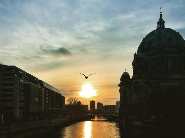 #paracegover Descrição para deficientes visuais: a imagem mostra o sol nascendo às nove horas da manhã em um dia que promete ser tão belo quanto frio. Ao fundo, a silhueta da Catedral de Berlim, à beira do rio Spree. Um pássaro cruza a cena. — at Museum Island.