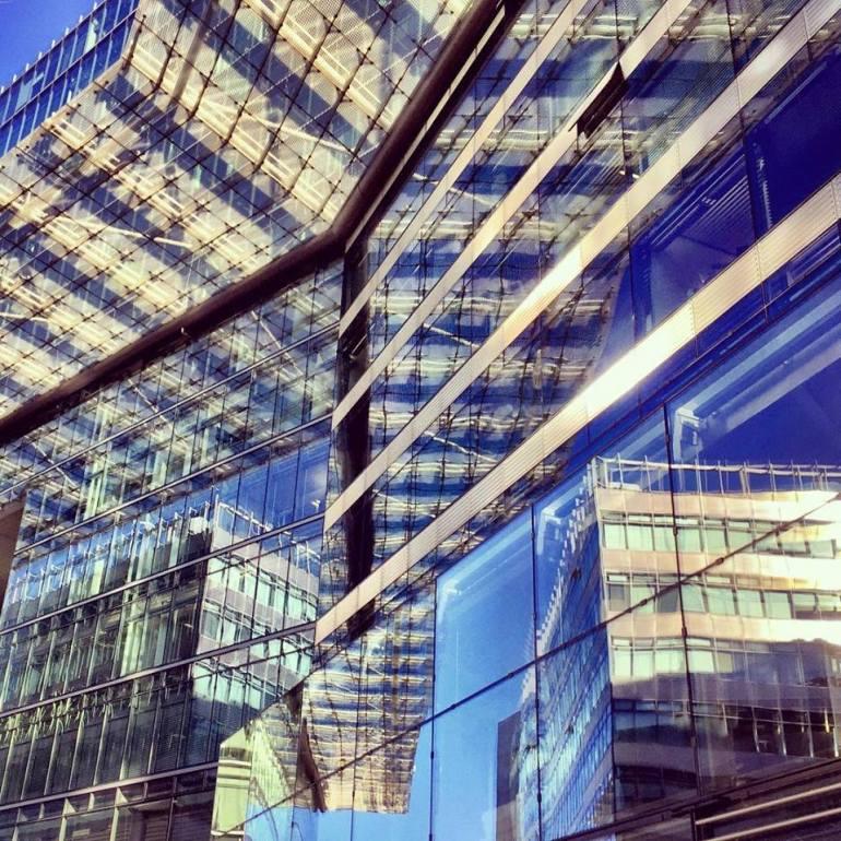 #paracegover Descrição para deficientes visuais: a imagem mostra um prédio espelhado fotografado de baixo para cima. A estrutura metálica se mistura ao vidro, formando padrões geométricos. O azul do céu é profundíssimo. — at Kurfürstendamm.