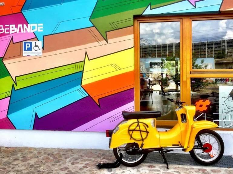 #paracegover Descrição para deficientes visuais: a imagem mostra uma vespa amarela estacionada em frente a uma fachada toda pintada com setas coloridas. — at Holzmarkt25.