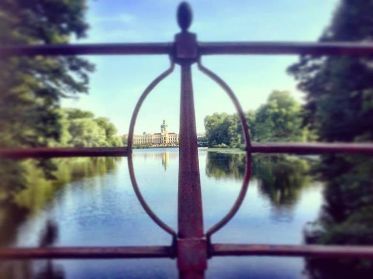#paracegover Descrição para deficientes visuais: a imagem mostra o Castelo de Charlottenburg em foco, ao fundo. A imagem é refletida no lado e é vista por entre os elementos geométricos do guarda-corpo de uma ponte. — at Schlosspark Charlottenburg.