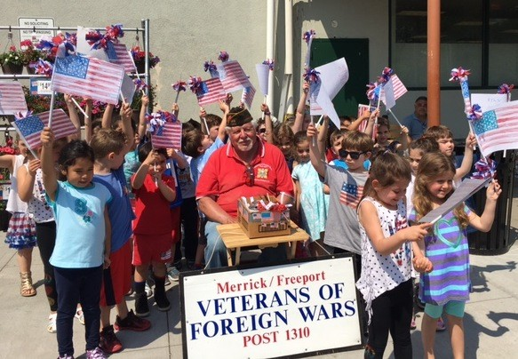 Students from the Jewish Early Learning Center Preschool and Camp surprised veteran Vincent Mientus, of Merrick, by waving home-made American flags as he collected donations for the Veterans of Foreign Wars before Memorial Day.