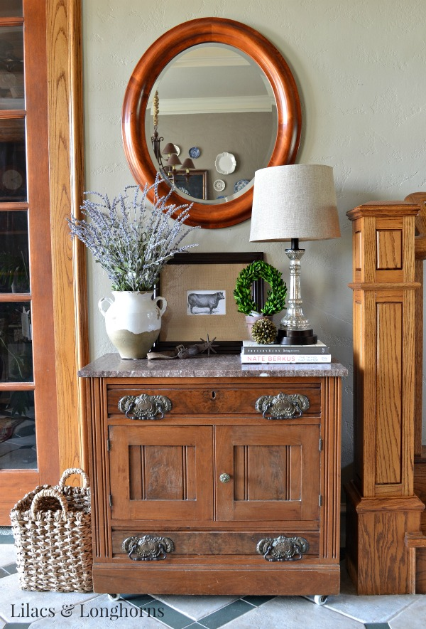 An antique cabinet styled with rustic touches.