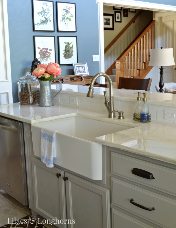 farm sink and marble counters in farmhouse traditional kitchen