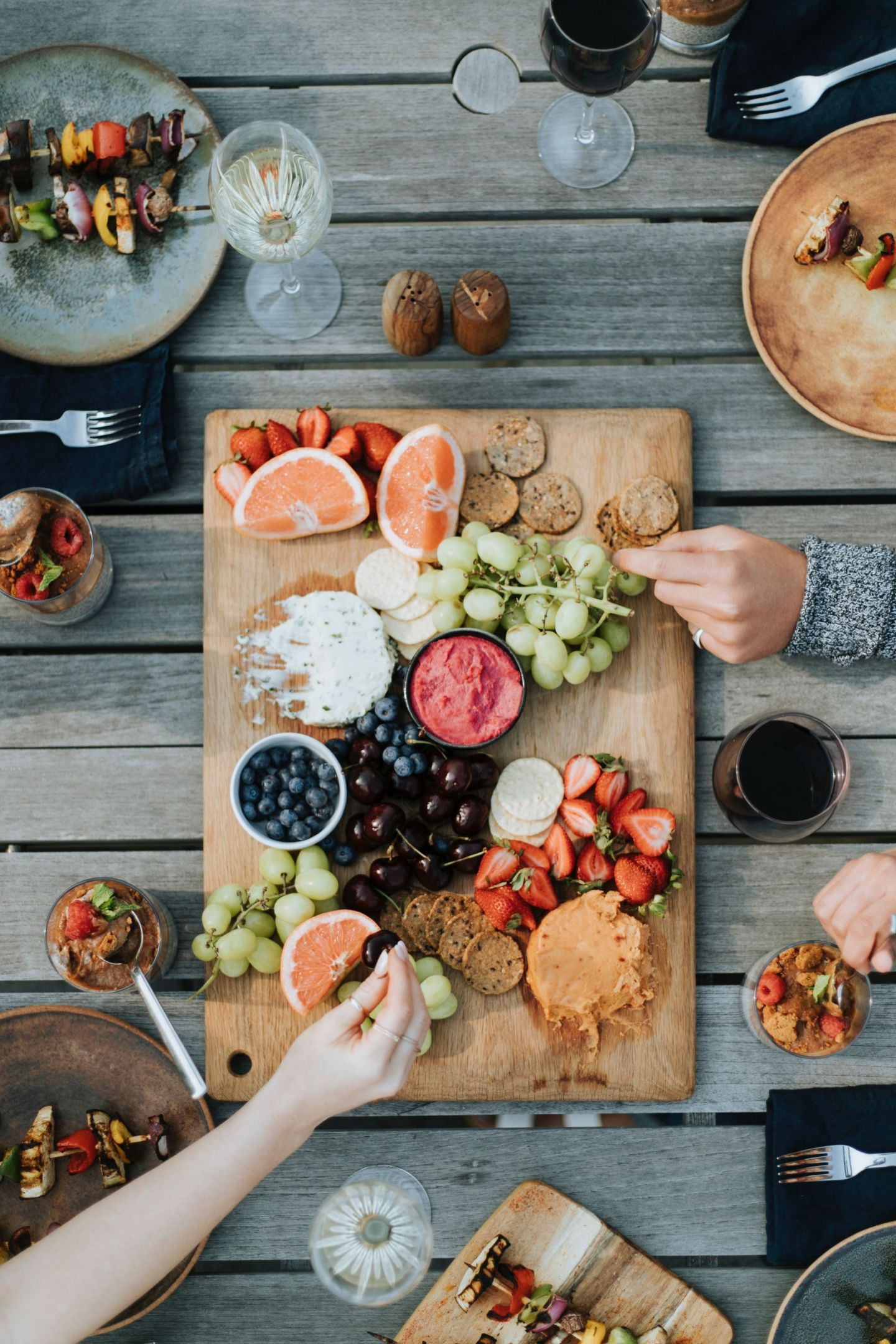 out door dining with various fruits, cheeses and crackers on a wooden board with friends eating it. A dining area is essential when getting your garden ready for summer