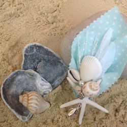 Image of Lilly Dilly's bespoke button holes made with sea shells and pale blue polkadot material laid on a pebble on the sand