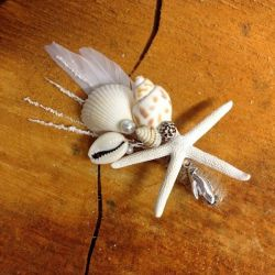 Image of Lilly Dilly's bespoke button holes made with sea shells and white feathers laid on a slice of wood