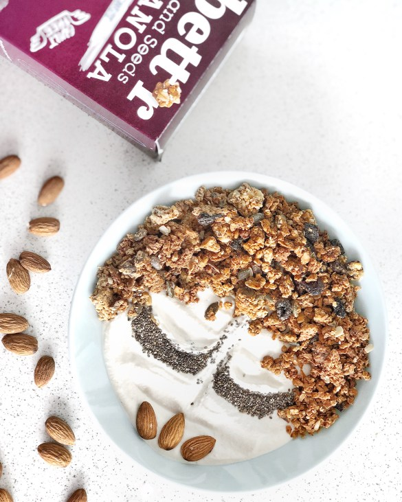 Cashew yoghurt with granola, chia and almonds arranged like a face in a bow