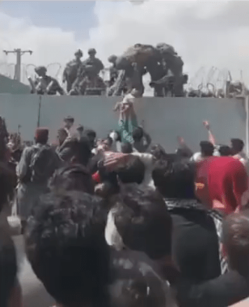 Afghan mum hands baby over barbed wire to American soldier for evacuation