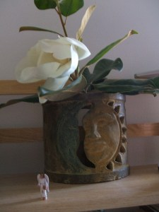 Magnolia blossom in sun face vase with angel figurine