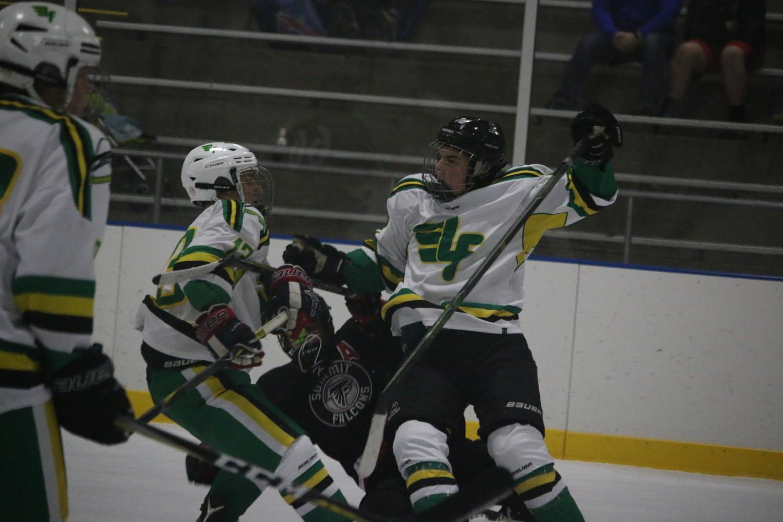 Forward, Hunter Heilmann (12, #13) and defense, Sam Hazelton (9, #27) knock over one of Summit's players.
