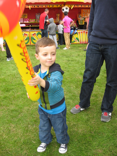 Child holding an inflatable hammer from the fun fare