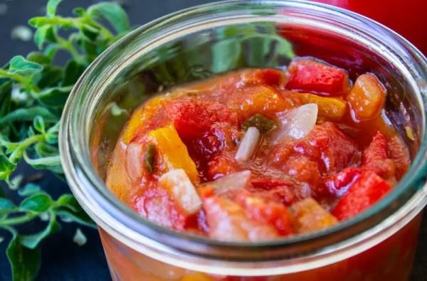Petit pot de compotée de tomates aux poivrons avec de l'origan
