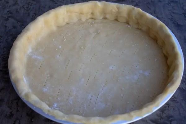 Moule rempli de pâte brisée préparée à la fourchette