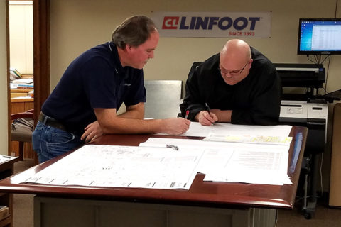 Engineers and estimators leaning over plans in discussion working