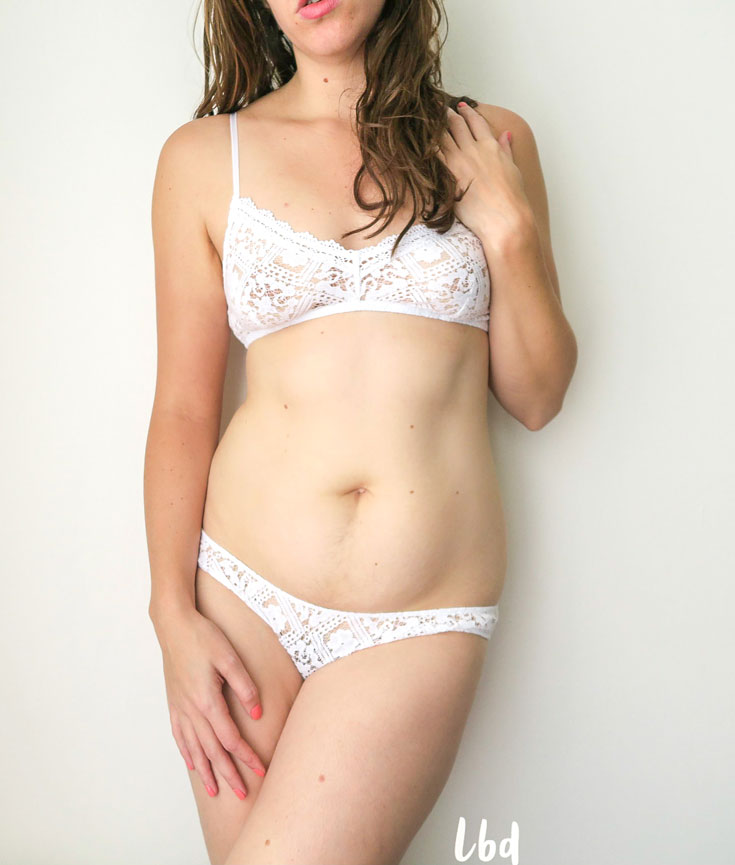 Liz wearing the Only Hearts Lisbon Lace bralette and brief, in white. The design is large repeating squares of a medieval square floral design.