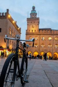 Foto di piazza Maggiore, Bologna, Italia. In primo piano una bicicletta e sullo sfondo piazza Maggiore illuminata.Bus Parma-Bologna