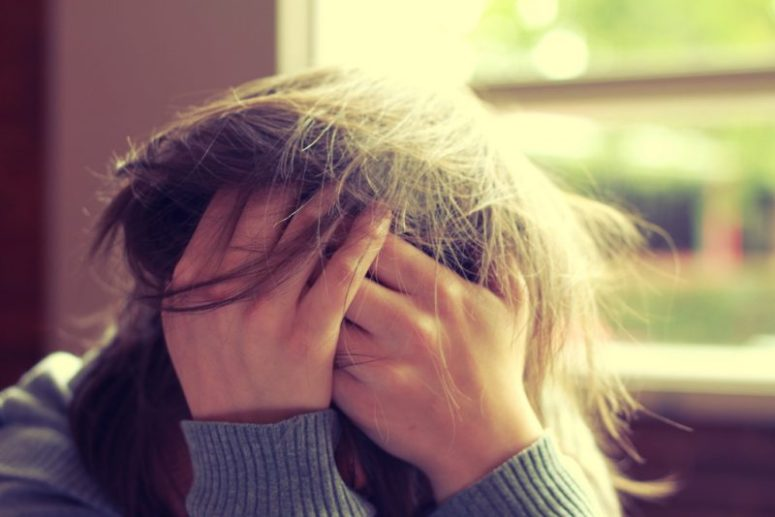 Woman holding her head in frustration