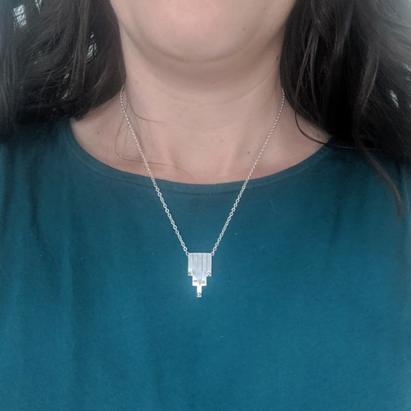 5-bar sterling silver necklace on teal shirt