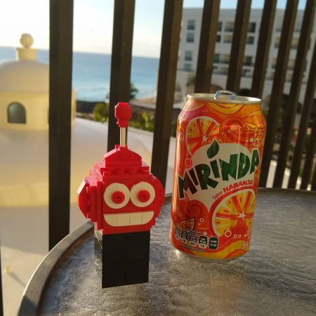 Lego robot next to orange soda on the balcony in Cancun