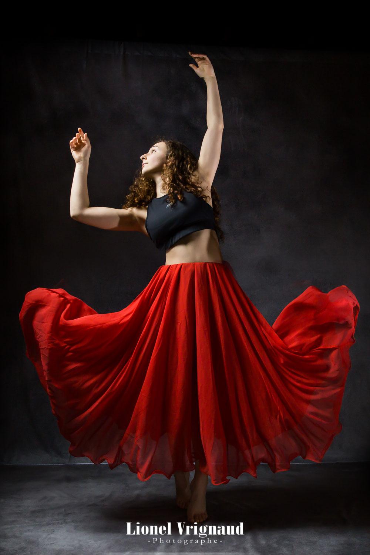 Une danseuse en robe tend les bars en l'air