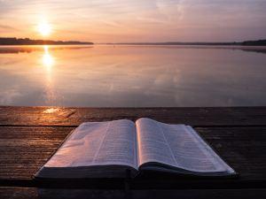 Bible and the horizon. Photo by Aaron Burden on Unsplash