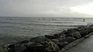 As the waves die, surfers hope for one more good set at Sheboygan's Deland Park.
