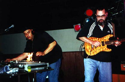 DJ Eddie Mills and Tommy Sanchez *literally* burn up the stage at Mulligan's in Richmond, Va. (April 2000).