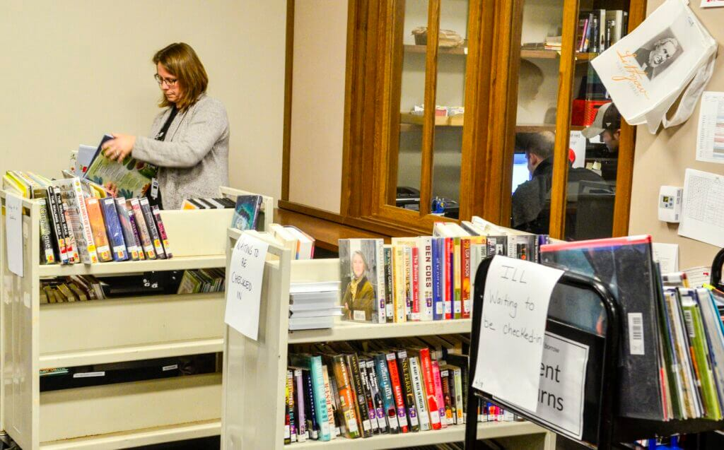 Women Sorts Books in Public Library, Cyberattack, Liquid Video Technologies