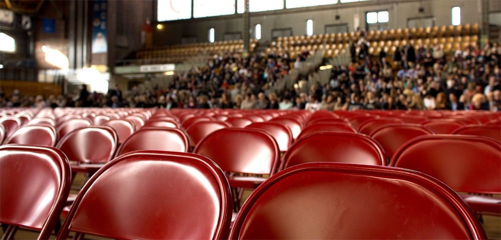 Rows of red folding chairs in auditorium