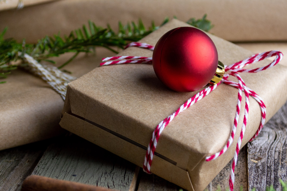 Brown-paper wrapped present tied with red and white twine, with red globe ornament on top.