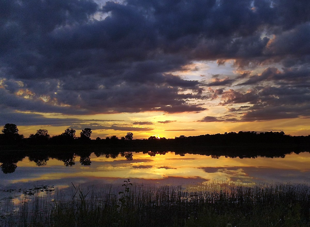 golden rays of the sunset against a deep blue-gray sky with tree lines silhouette reflected in the calm waters of the lake.