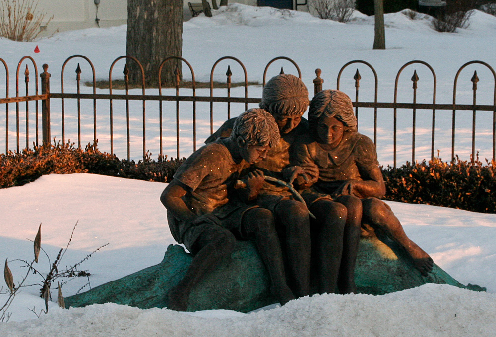 bronze sculpture of three children reading