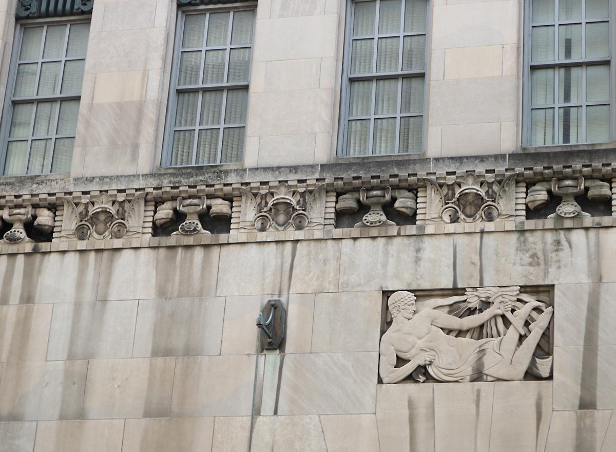 ornate limestone frieze below the first row of windows surrounding the skyscraper