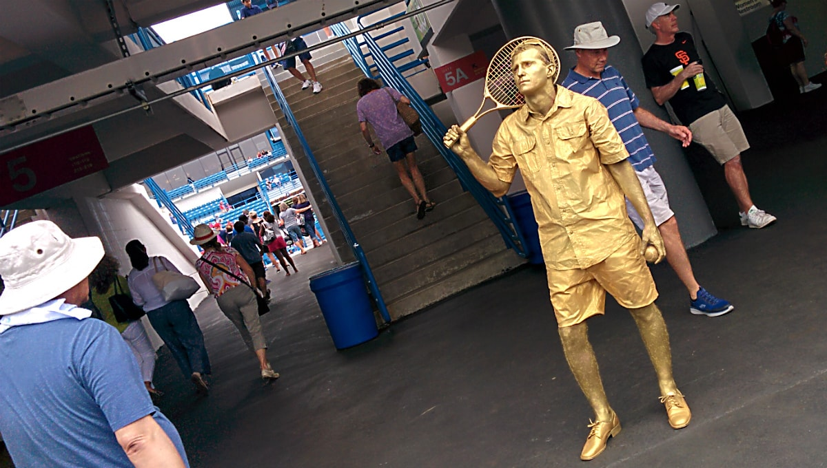 gold-covered actor dressed as a tennis player stands near Center Court entrance as people walk by