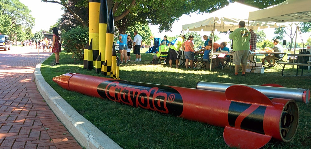Red Crayola rocket laying on the ground, with yellow rockets and people outside on the Henry Ford front lawn
