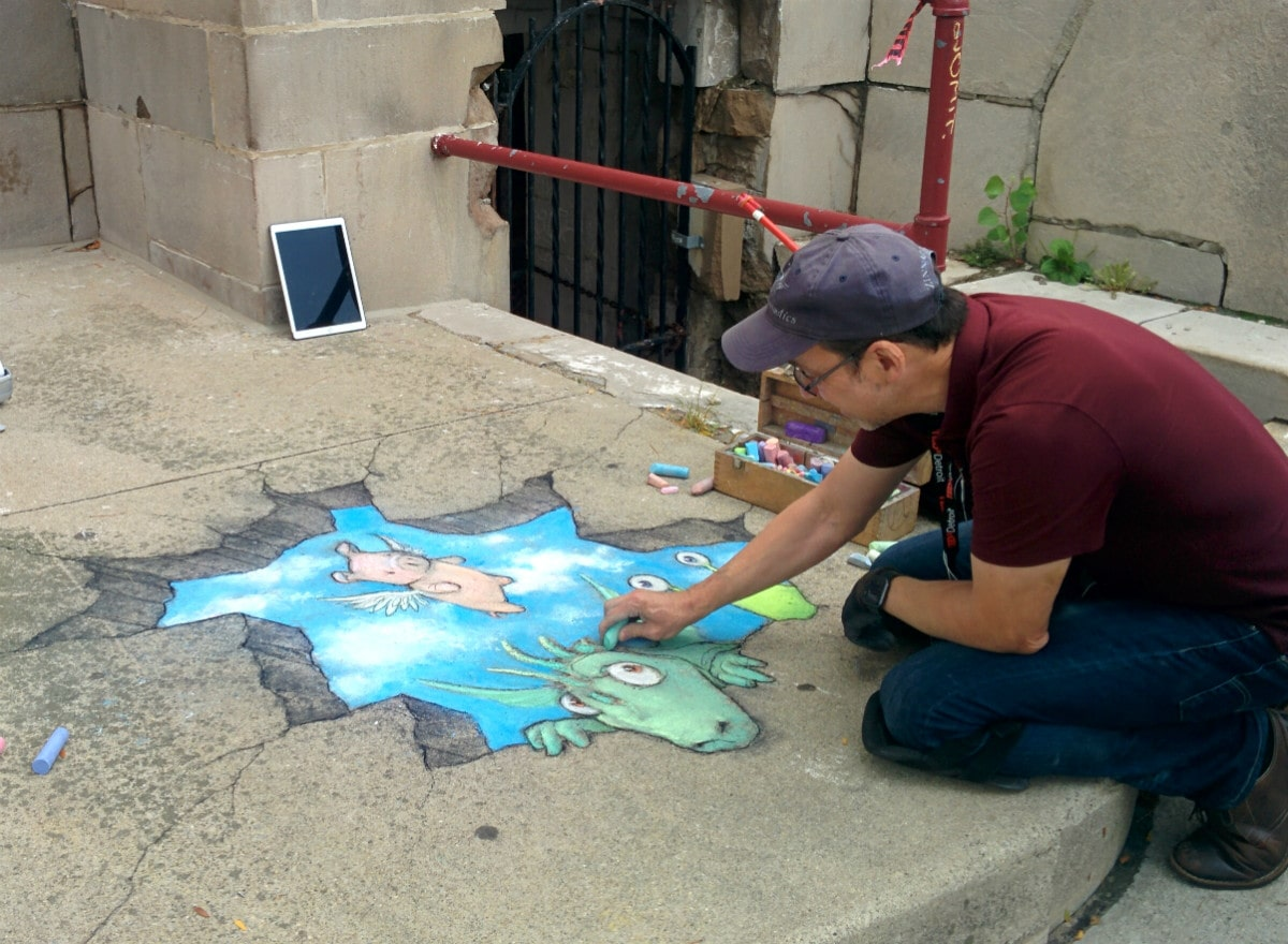 Artist David Zinn completes coloring Philomena the flying pig and Sluggo, the green monster on the porch of Masonic Temple.